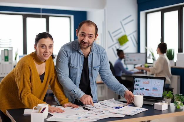 Multiethnisches management lächelt und arbeitet daran, das projekt zu beenden und zeigt auf diagramme auf dem schreibtisch