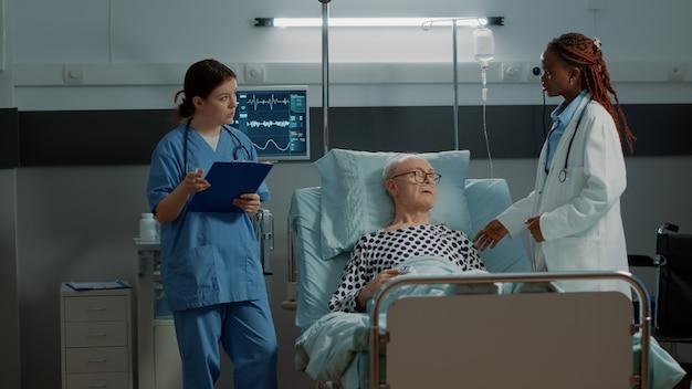 Multiethnisches medizinisches team, das den puls am patienten überprüft