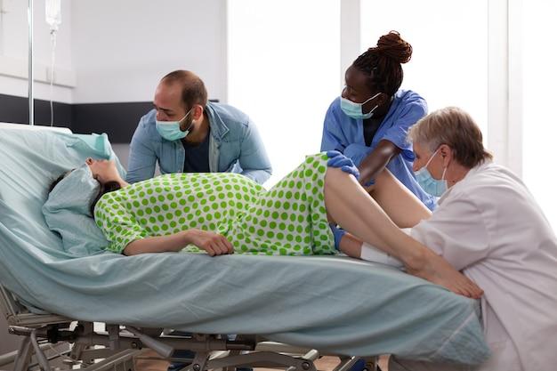 Multiethnisches medizinisches team, das die geburt einer frau unterstützt