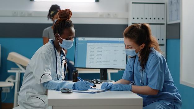 Multiethnisches medizinisches team, das über die behandlung von patienten spricht