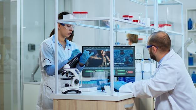 Multiethnisches team, das dna-mutation untersucht, arzt, der tests aus röhrchen überprüft, während die krankenschwester notizen in der zwischenablage macht. wissenschaftler untersuchen die virusentwicklung mit hilfe von hightech für die erforschung der impfstoffentwicklung