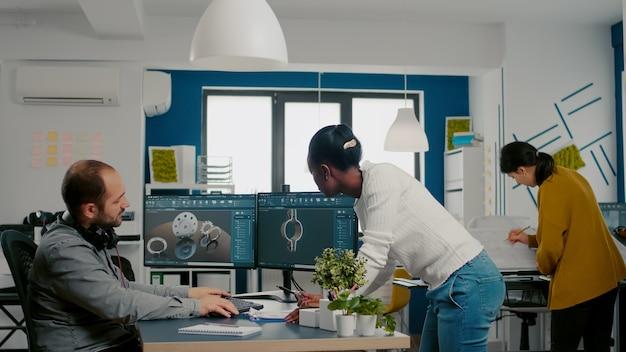 Multiethnisches team, das ideen zu industrieprojekten mit zwei monitoren mit d-zahnrädern und metallischen ...
