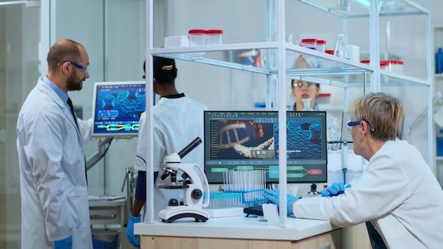 Multiethnisches team, das in einem modern ausgestatteten labor an der entwicklung eines neuen impfstoffs arbeitet. diverse gruppe von biochemie-wissenschaftlern, die die virusevolution mit hightech für die erforschung von behandlungen untersuchen