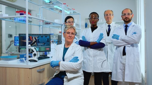 Multiethnisches team erfahrener wissenschaftler, die in einem modern ausgestatteten labor in die kamera schauen. gruppe von ärzten, die die virusentwicklung mit hightech- und chemiewerkzeugen für die wissenschaftliche forschung, impfstoffentwicklung untersuchen