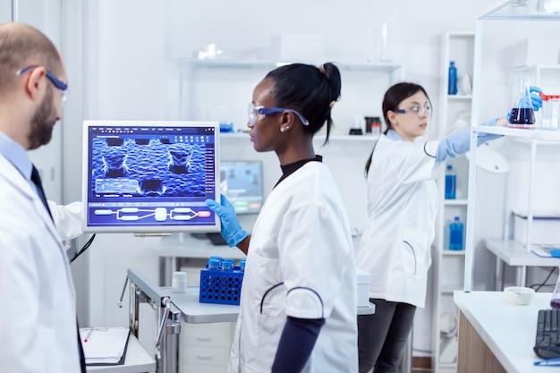 Multiethnisches team medizinischer forscher, die im sterilen labor mit schutzbrille und handschuhen zusammenarbeiten.