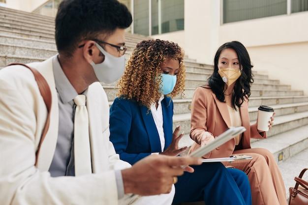 Multiethnisches team von ernsthaften geschäftsleuten, die in schutzmasken auf stufen sitzen und über die gründung eines neuen geschäfts während einer pandemie sprechen
