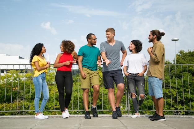 Multiethnisches team von freunden, die auf brücke plaudern