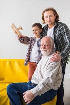 Multigenerationale männer, die kamera umarmen und betrachten