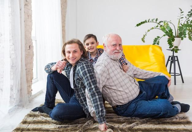 Multigenerationale männer, die zu hause auf teppich sitzen