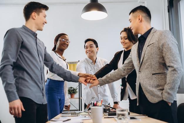 Multikulturelle euphorische business-team-leute geben high-five am bürotisch, glücklich aufgeregt vielfältige arbeitsgruppe im teambuilding feiern unternehmenserfolg gewinnen partnerschaft power teamwork-konzept