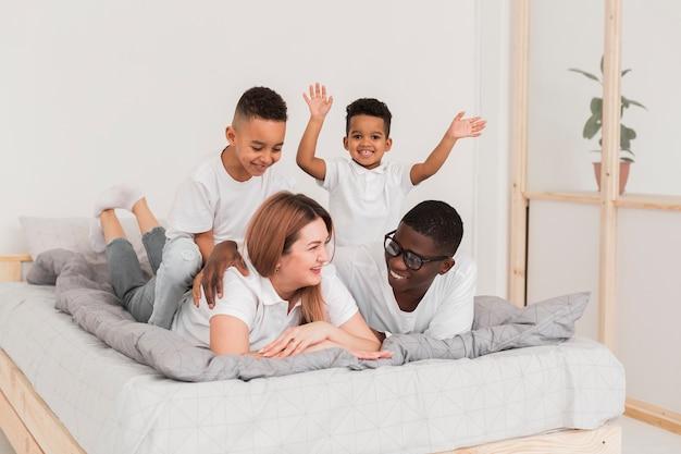 Multikulturelle familie, die zusammen im bett bleibt