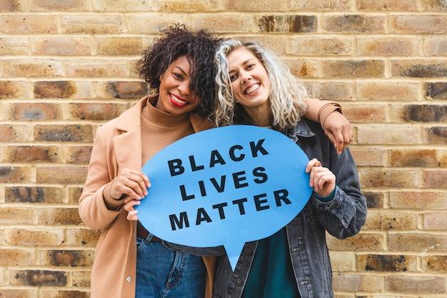 Multikulturelle frauen, die eine gedankenblase mit schwarzer lebensmaterie halten - glückliches gemischtrassiges paar an einem tag in der stadt - konzepte für freundschaft, lebensstil und teamarbeit