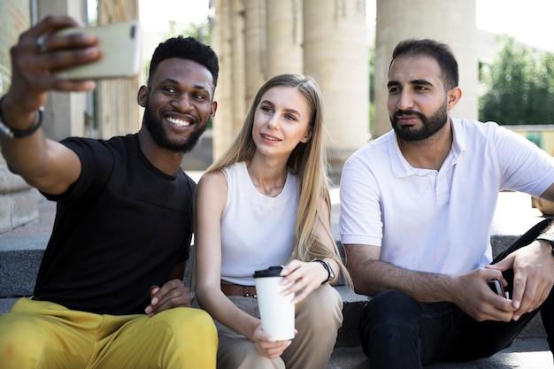 Multikulturelle freunde des mittleren schusses, die selfies nehmen