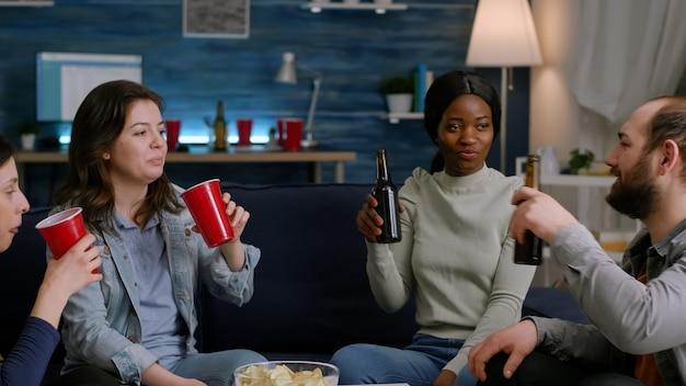 Multikulturelle freunde, die sich während der nächtlichen party zu hause unterhalten, während sie sich auf dem sofa entspannen