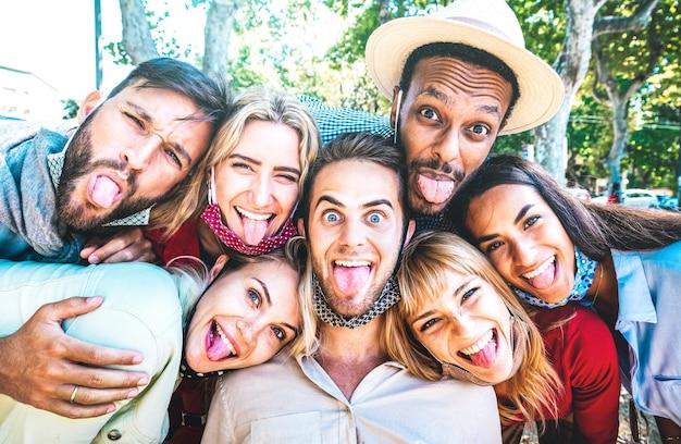 Multikulturelle freunde, die während der dritten welle von covid 19 ein verrücktes selfie nehmen, das die zunge herausstreckt
