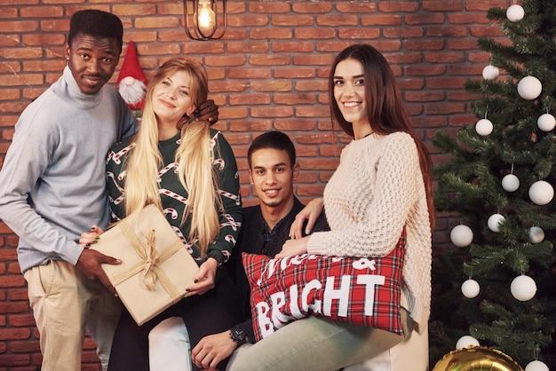 Multikulturelle freunde, die zusammen zu hause am weihnachtsabend stillstehen