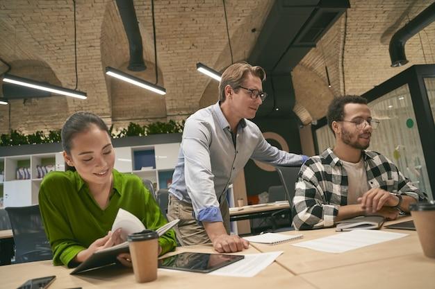Multikulturelle geschäftsleute, die gemeinsam an einem projekt im modernen büro arbeiten, überzeugter kaukasier