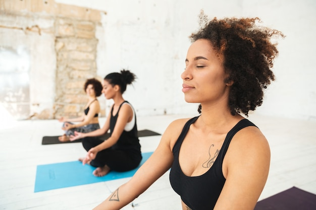 Multikulturelle gruppe, die yogaübungen auf matten macht