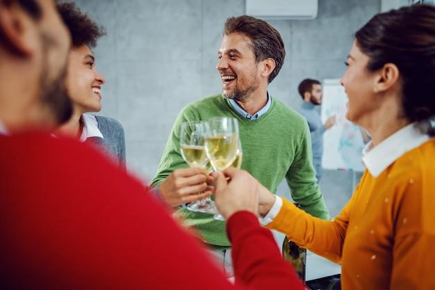 Multikulturelle gruppe von kollegen, die den erfolg im sitzungssaal feiern. kollegen, die mit champagner anstoßen.