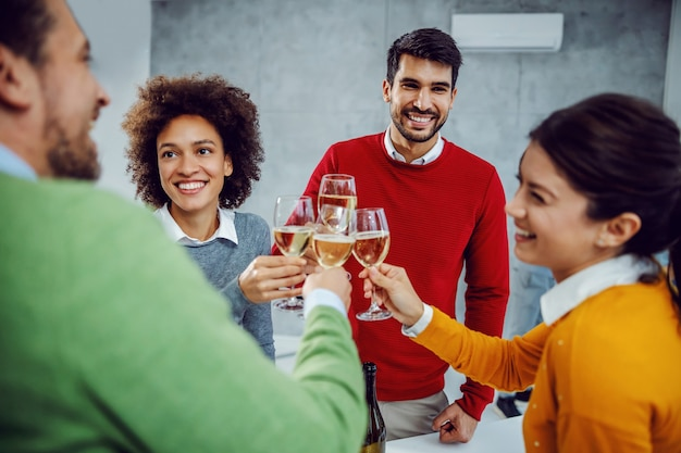 Multikulturelle gruppe von kollegen, die im sitzungssaal erfolge feiern. kollegen, die mit champagner rösten.
