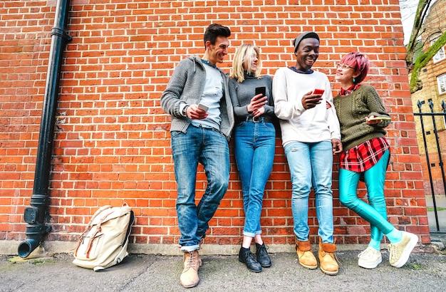 Multikulturelle hipster-freunde, die inhalte auf smartphone im stadtgebiet in shoreditch london teilen