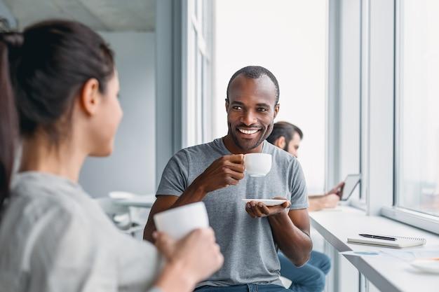 Multikulturelle kollegen scherzen während der kaffeepause am arbeitsplatz