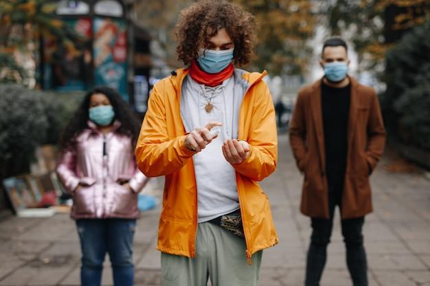 Multikulturelle menschen in medizinischen masken, die auf der stadtstraße stehen und antiseptikum verwenden. junge freunde, die während der pandemie soziale distanz halten.