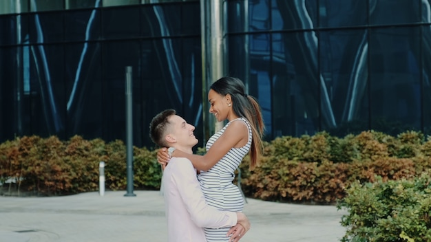 Multikulturelles familienkonzept: ehemann dreht sich um seine frau, während er die straße entlang geht