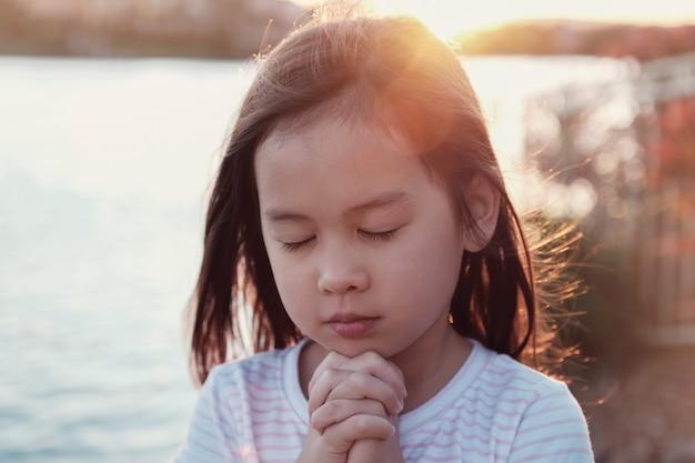 Multikulturelles kleines mädchen, das mit sunflare hintergrund betet