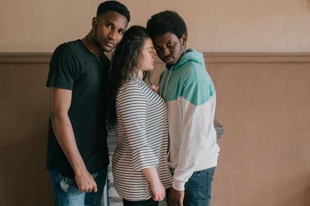 Multikulturelles liebes- und beziehungskonzept. junge weiße frau, die nahe zwischen zwei dunkelhäutigen afrikanischen männern steht. innenporträt von interracial liebenden trios. zwei afrikanische männer umarmen ihre freundin