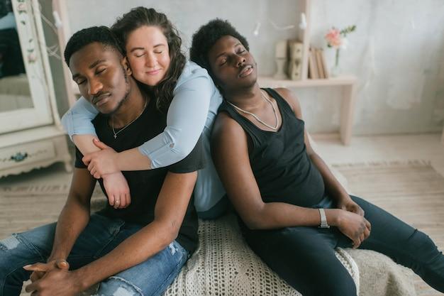 Multikulturelles liebes- und beziehungskonzept. junge weiße frau sitzt und umarmt mit zwei afrikanischen dunkelhäutigen männern. weichzeichner-studio-porträt des interracial umarmenden paares. interracial liebende trios