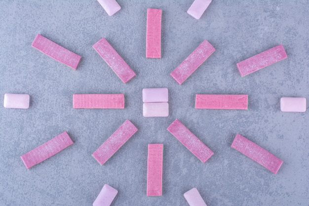Multilineare anordnung von kaugummistreifen und -tabletten auf marmoroberfläche