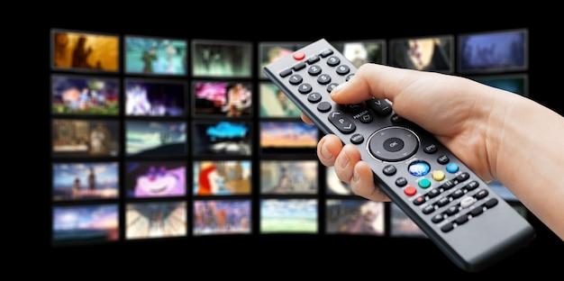 Multimedia-fernsehbildschirm und menschliche hand mit fernbedienung