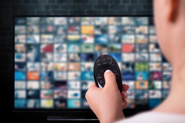 Multimedia-streaming-konzept. frau hält fernbedienung. fernsehbildschirm mit vielen bildern.