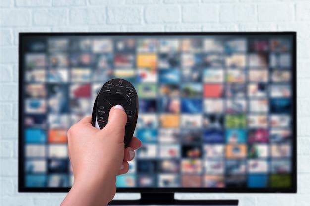 Multimedia-streaming-konzept. weibliche hand hält fernbedienung. vod-inhaltsanbieter