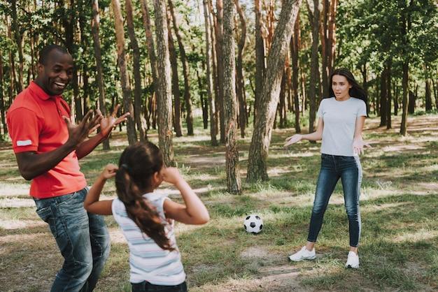 Multinationale familie, die mit ball im wald spielt.