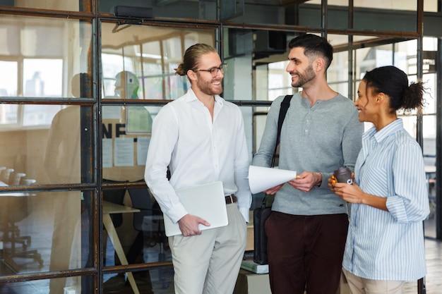 Multinationale zufriedene kollegen sprechen und lächeln, während sie in einem modernen büro stehen