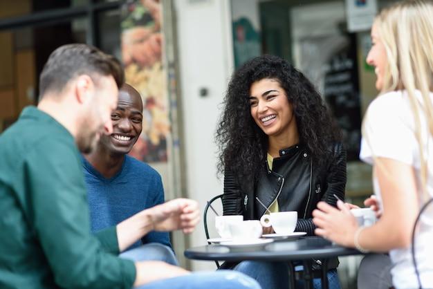 Multiracial gruppe von vier freunden mit einem kaffee zusammen