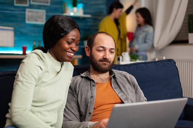Multirassische freunde, die sich beim anschauen von online-videos auf dem laptop auf dem sofa treffen. im hintergrund verbringen zwei frauen, die bier trinken, die zeit zusammen während der unterhaltungsparty.