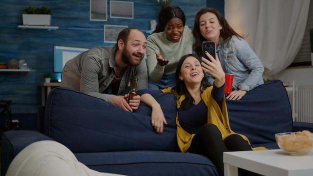 Multirassische freunde, die während der videoanrufkonferenz mit einem modernen smartphone mit einem kollegen sprechen. gruppe multiethnischer menschen, die zusammen rumhängen, bier trinken, spaß während der nachtparty haben?
