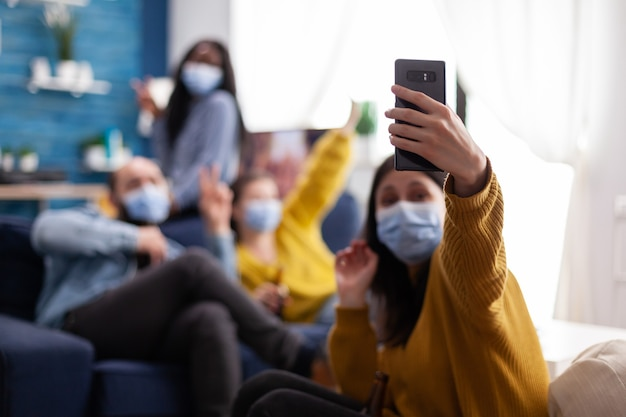 Multirassische freunde, die während des ausbruchs von covid 19 selfie mit gesichtsmasken machen, neues normales lifestyle-konzept mit menschen, die spaß im wohnzimmer haben und die soziale distanz respektieren, um die ausbreitung des virus zu verhindern