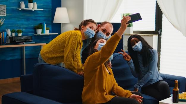 Multirassische freunde, die während des ausbruchs von covid 19 selfie mit gesichtsmasken machen, neues normales lifestyle-konzept mit menschen, die spaß im wohnzimmer haben und die soziale distanz respektieren, um die ausbreitung von viren zu verhindern