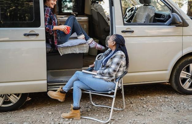 Multirassische freundinnen, die spaß beim campen im wohnmobil im freien im wald haben - fokus auf älterem afrikanischen frauengesicht