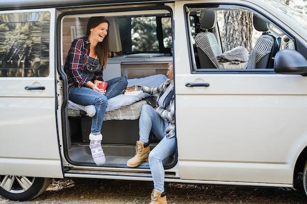 Multirassische freundinnen, die spaß haben, im wohnmobil im freien im wald zu campen - fokus auf das gesicht der älteren afrikanischen frau