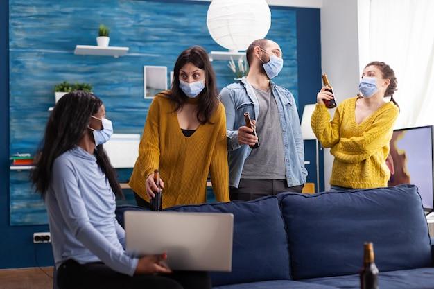 Multirassische gruppe von freunden, die mit laptop chatten, soziale distanz halten und gesichtsmaske tragen, um die ausbreitung und infektion von covid im wohnzimmer der wohnung zu verhindern konzeptionelles bild