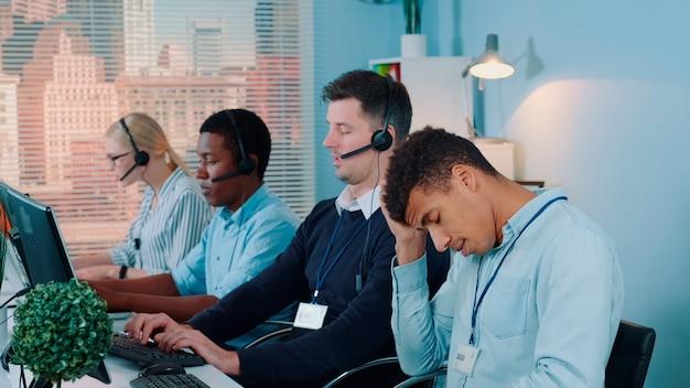 Multirassischer call-center-agent, der sich nach dem telefonat mit dem kunden erschöpft und niedergeschlagen fühlt. er arbeitet mit einem gemischtrassigen team in einem modernen büro.