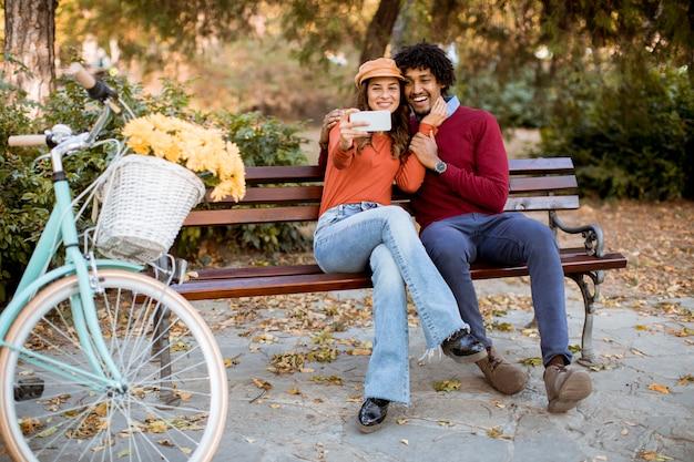 Multiratial liebevolle paare, die auf bank sitzen und selfie mit handy im herbststadtpark nehmen