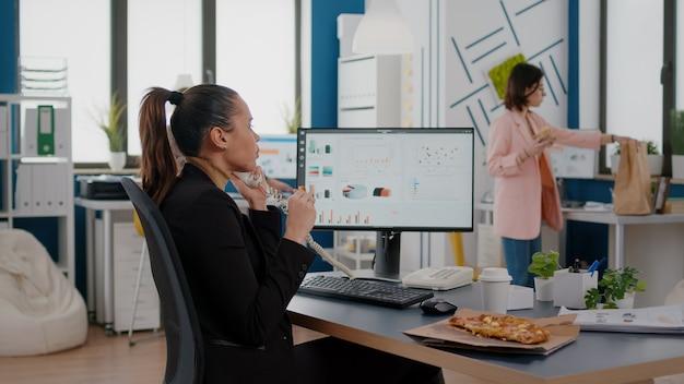 Multitasking-geschäftsfrau, die über das festnetz spricht und einem remote-kollegen firmendiagramme erklärt, während sie am schreibtisch eine essensbestellung zum mitnehmen hat