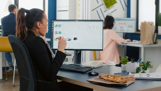 Multitasking-geschäftsfrau diskutiert marketingstrategie mit remote-mitarbeiter über festnetz, während sie in der mittagszeit ein pizzastück isst eating