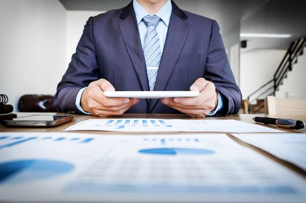 Multitasking. handsome junge mann arbeitet mit touchpad beim sitzen auf der couch im büro und finanzielle statistische grafik.